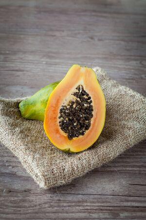 Sliced fresh papaya fruit on wooden background Stockfoto