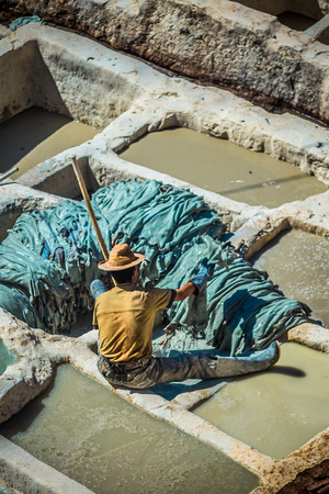 smells: Tanners working leather in the old tannery of Fes, Morocco Stock Photo