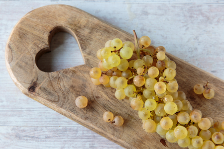 whine: Fresh white whine grapes on a chopping board