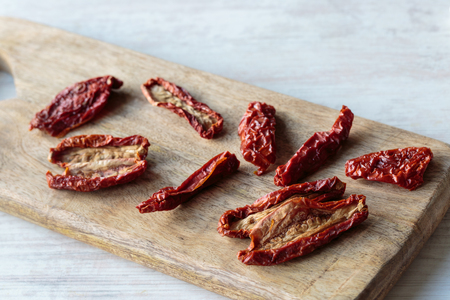 sundried: Delicious dry tomatoes on a chopping board Stock Photo