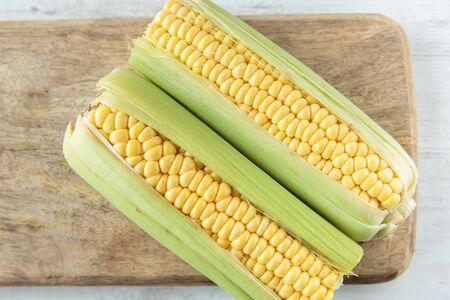 corncob: Fresh raw corncob on a chopping board