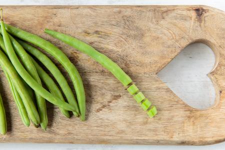 ejotes: primas jud�as verdes frescas en una tabla de cortar