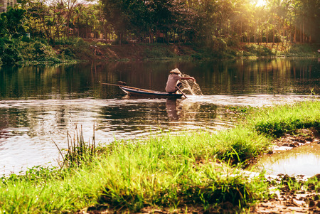 Man fishing on a river in Hoi An, in Vietnam Stock Photo