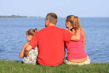 A young father looks at the sailboats with his girls Stock Photo - 5440995