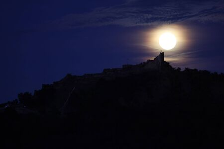 A full moon is  above a Szigliget  castle photo