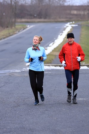 Two people running in the cold winter weather photo