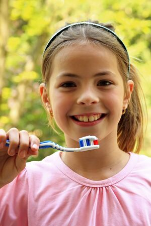 Happy, young girl shows us how important is to brush teeth.