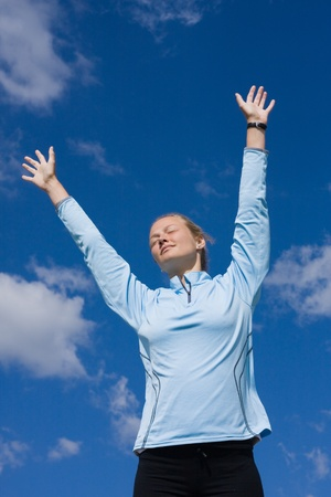 rightly: A pretty young woman stretching toward the sky Stock Photo