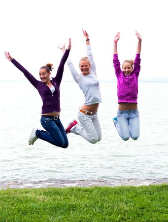 Happy young girls jumping on the shore