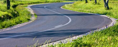 Beautiful curved asphalt road on sunny day photo