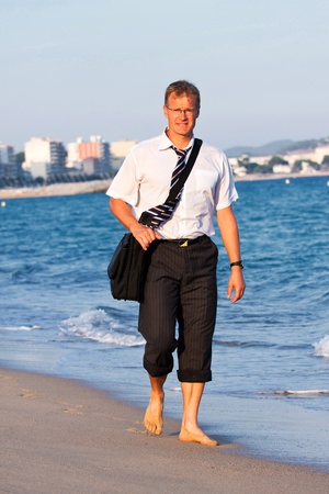 Blond , young businessman walks close to the sea photo