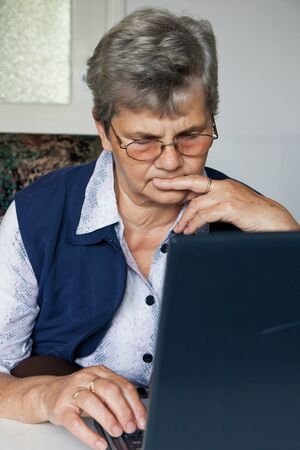 Senior lady learns with the computer photo