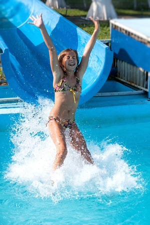 aqua park: Pretty young girl joy in the water slides  Stock Photo