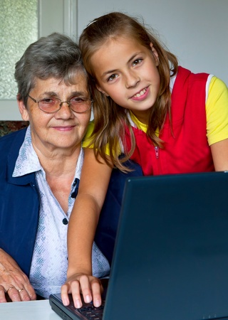 Grandchild teach your grandmother to play with a computer  photo