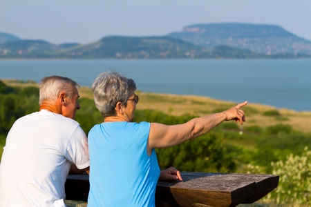 Elderly couple sitting at the lakeside bench Stock Photo