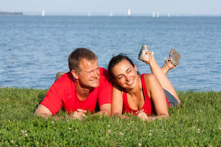 Joyful young couple is overlaping shore of the lake  photo