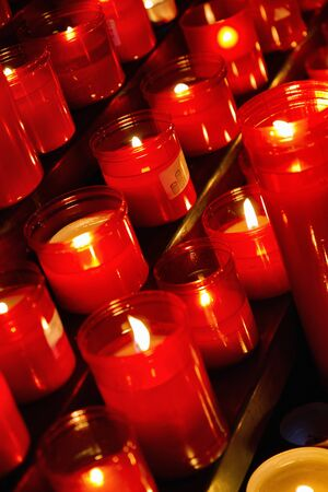 Church candles in red  transparent chandeliers  photo