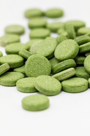 Green chlorophyll tablets on white