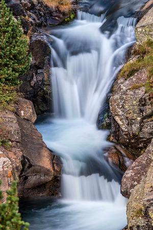 gauzy: Beautiful veil cascading waterfall, mossy rocks Stock Photo