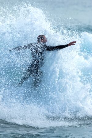 shorebreak: Surfer on Blue Ocean Wave with many drops Stock Photo