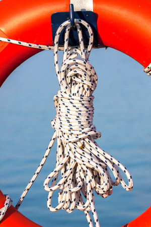 buoy: Orange life buoy with rope Stock Photo