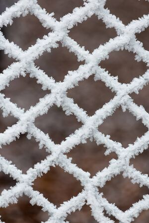 Frozen fence on a cold winter day