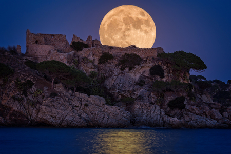 Full moon over the old castle in Costa Brava in a holiday village Fosca , Spain