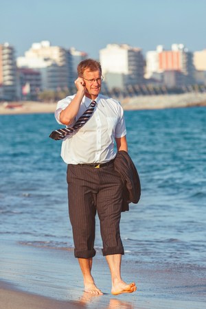 Young businessman walking on th e beach after the work time