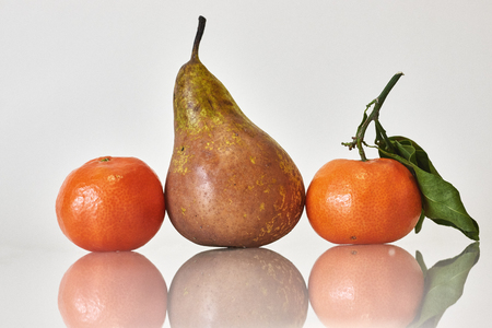 Tree fruits on white background, pear and oranges Imagens