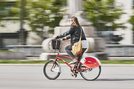 Young woman go to work with special renting bike, Bicing, in Barcelona of Spain. Long exposure technique picture. 15. 04. 2015 Spain