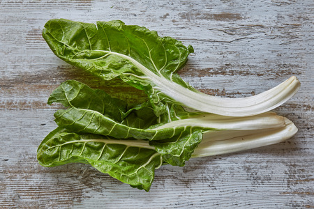 Healthy vegetable chard on a rustic wooden board. Plant, cuisine