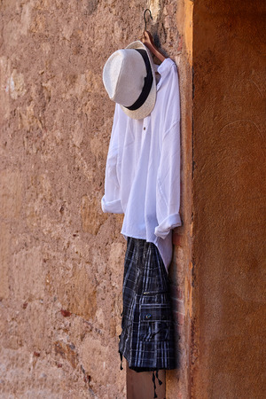White dress and hat hanging on the red wall
