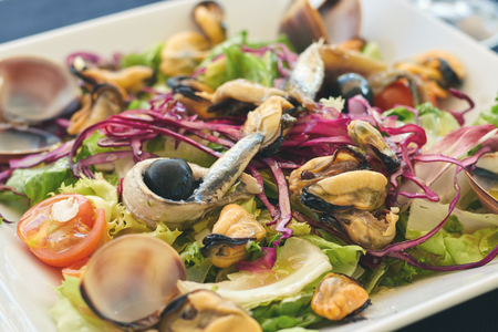 Typical Spanish salad with seafood and anchovies on the restaurant