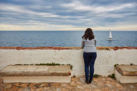 Woman looking at infinite sea and sailboat