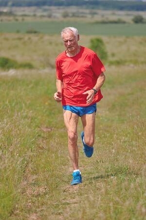 Senior runner running on the meadow at springtime