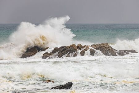 Big waves splashing on a rock in a spanish coastal, near the town Palamos in Costa Brava 写真素材