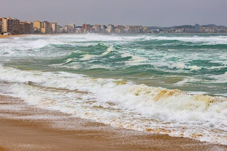 Big waves splashing on the beach in a spanish coastal, near the town Palamos in Costa Brava