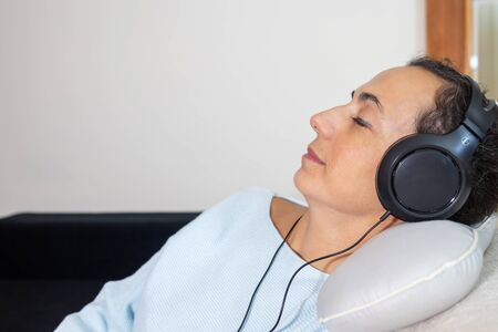 Young Spanish woman listening to music at home with headphones