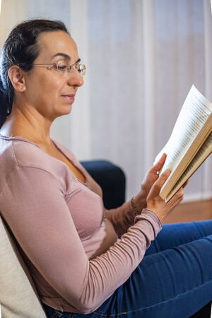 Pretty spanish women reading at home on the sofa