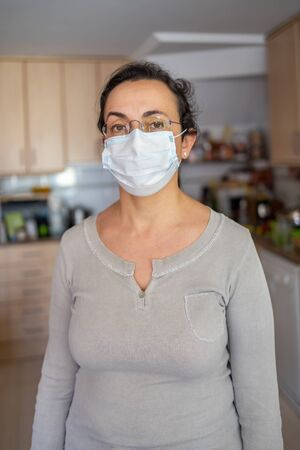 Middle aged woman with protective mask at home due to coronavirus quarantine
