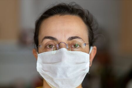 Young Spanish woman in protective sterile medical mask on her face looking at camera at home