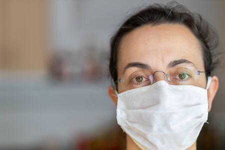 Young Spanish woman in protective sterile medical mask on her face looking at camera at home Stock fotó