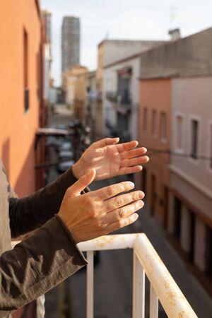 Woman applauding in a balcony of Spain greeting for works of doctors, nurses, policies during the coronavirus epidemic 版權商用圖片 - 147880844