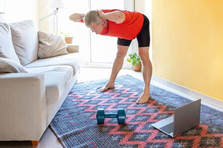 Blonde caucasian man practice online gymnastics at home in the living room