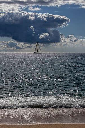 Dramatic sky over the Mediterranean sea, Costa Brav in Spain. Sailboat swimming far a way.