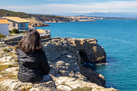 Woman sitting on the rock and looking at Costa Brava landscape from Spain, near the small village Montgo Banque d'images