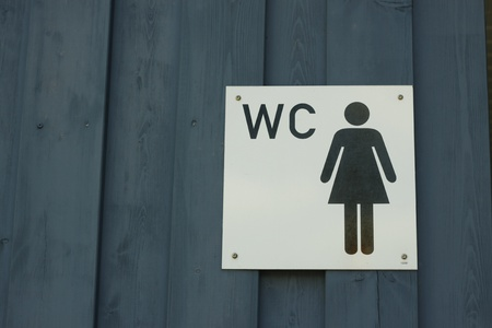 loo: White sign ladies room at blue wooden wall