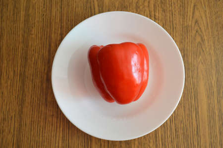 Red bell pepper on white food plate on wooden background. Healthy vegetarian organic dinner cooking