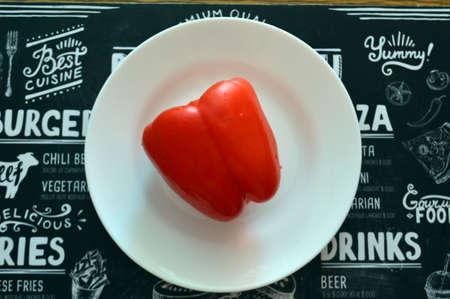 Red bell pepper on white food plate on black background. Healthy vegetarian organic dinner cooking