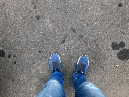 Person leg foot shoe on pavement road asphalt street. Outdoor road with jean man urban walk way concept. Sneaker standing on ground one person view. Hipster selfie top space. Photography image